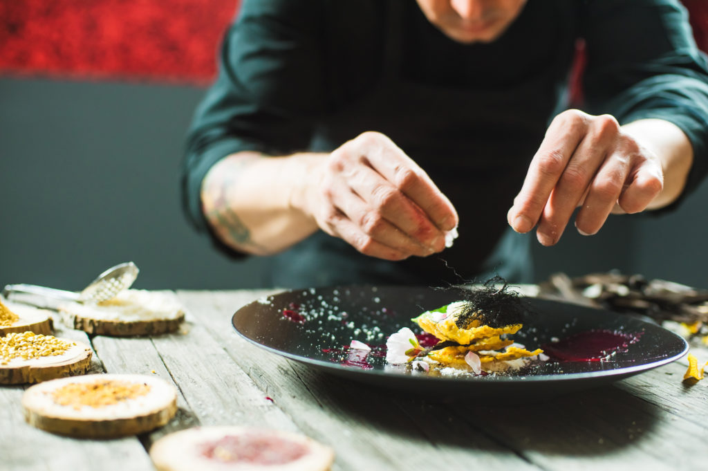 Close-up of male chef plating a molecular dish