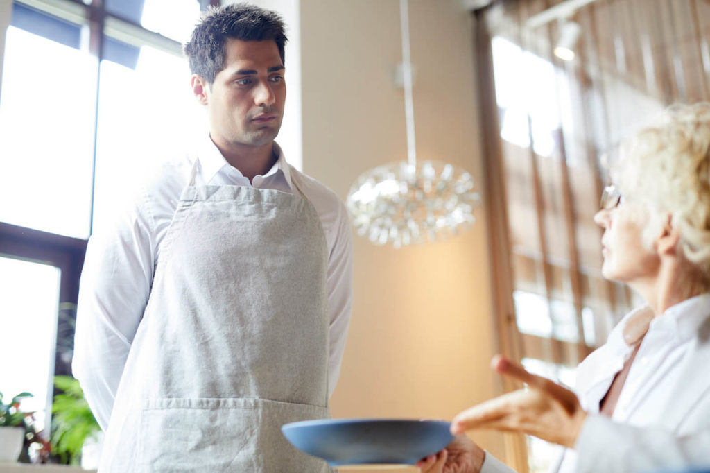 Young male waiter with an apron listening to an older woman client complaining about dish
