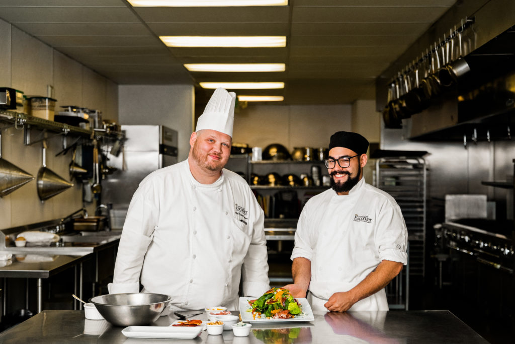 Escoffier chef instructor and smiling male culinary student with mixed vegetable plate
