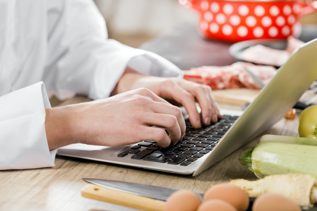 Chef typing on laptop computer on table with knife, eggs, and vegetables