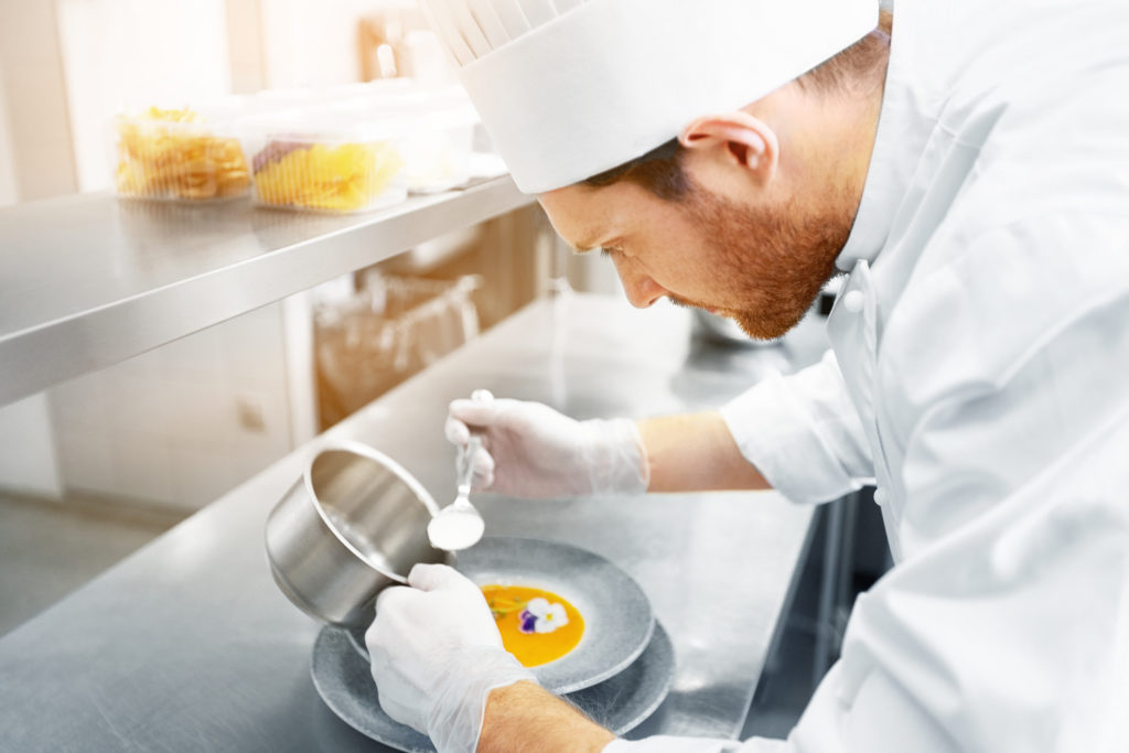 male chef cook serving and plating plate of soup with flower at restaurant kitchen