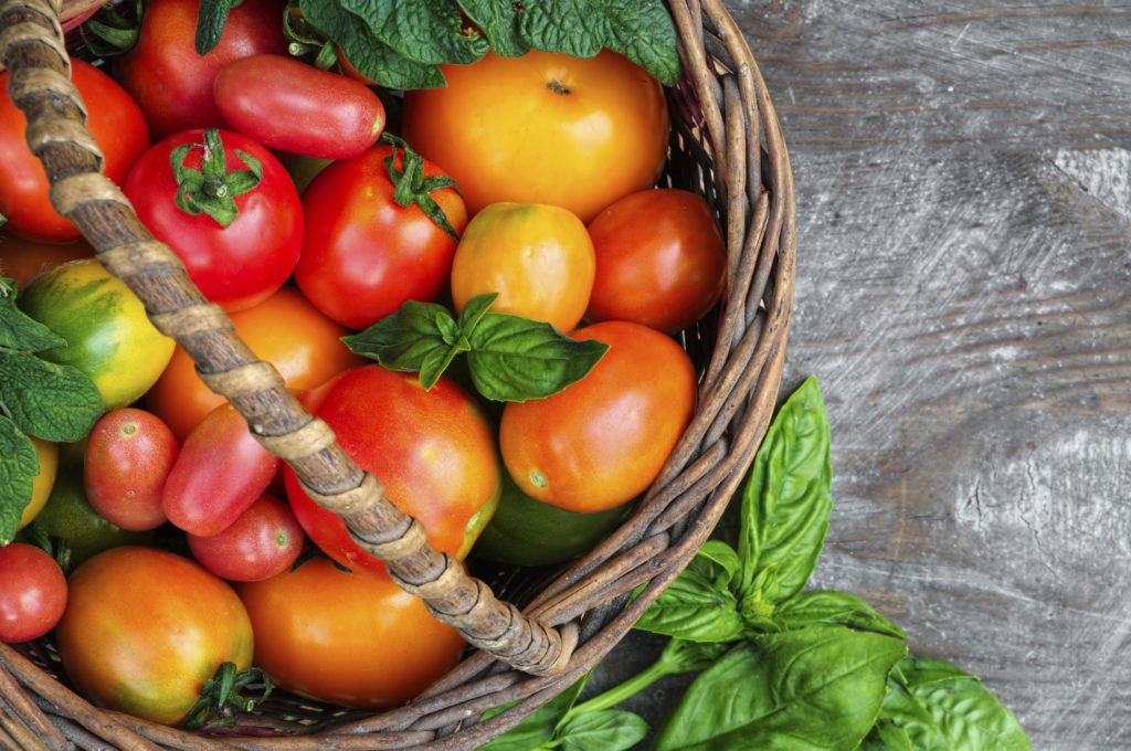 brown basket with red tomatoes