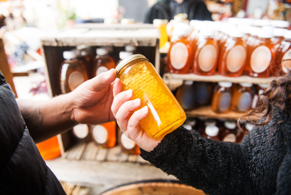 People looking at local honey.