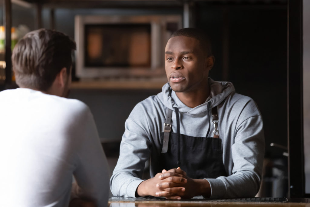 Black male chef talking with caucasian male vacancy candidate in restaurant