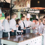 Restaurant manager and his staff in terrace interacting with head chef in restaurant