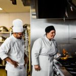 Female culinary student frying vegetables while chef instructor watches