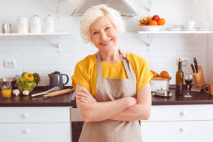 Happy older woman in apron preparing breakfast, crossed hands