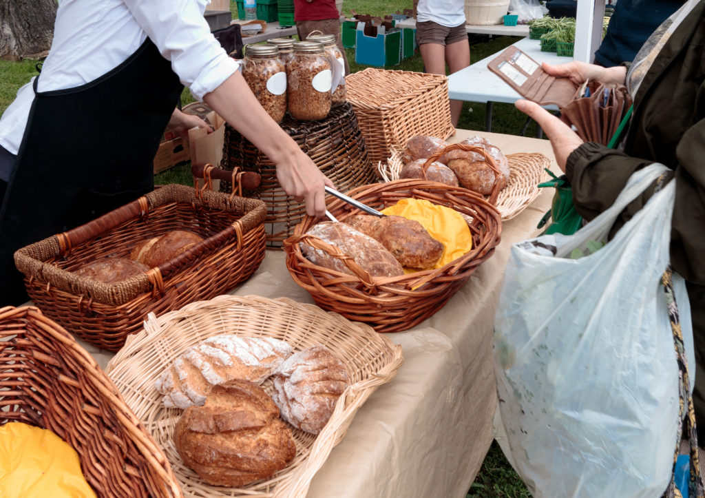 Woman selling organic bread at outdoors farmers market
