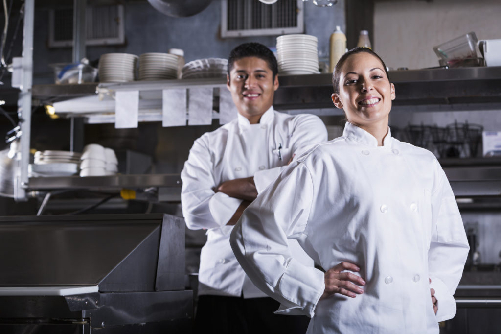 Smiling male and female cooks in commercial kitchen