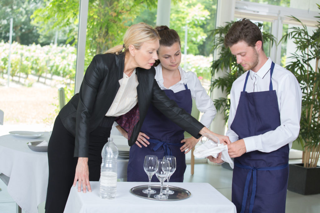 young male and female worker in apron and female manager at a venue banquet