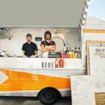 Two smiling men in a food truck huevos estrellados