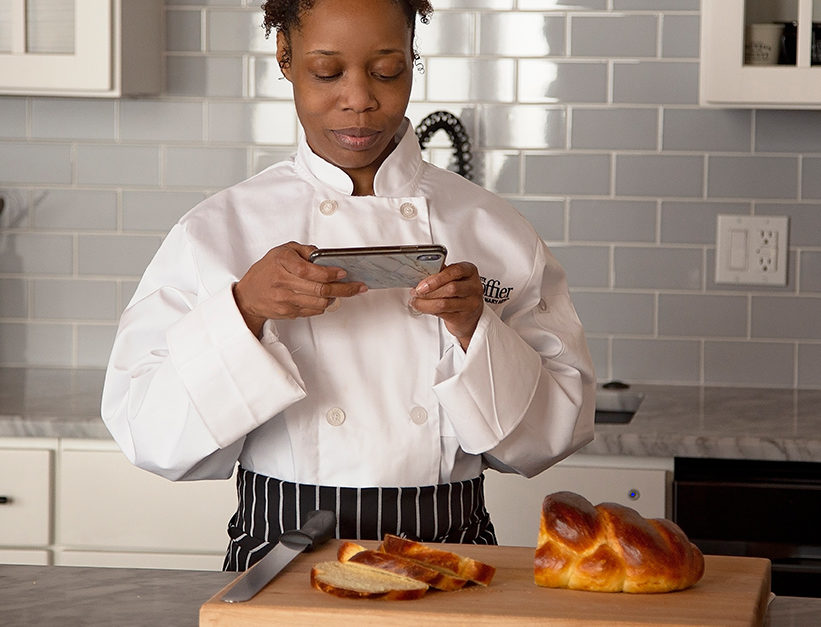Escoffier online student taking photo on phone of bread