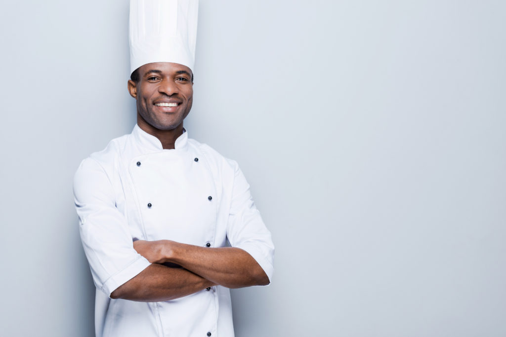 Smiling male black chef with white coat and hat