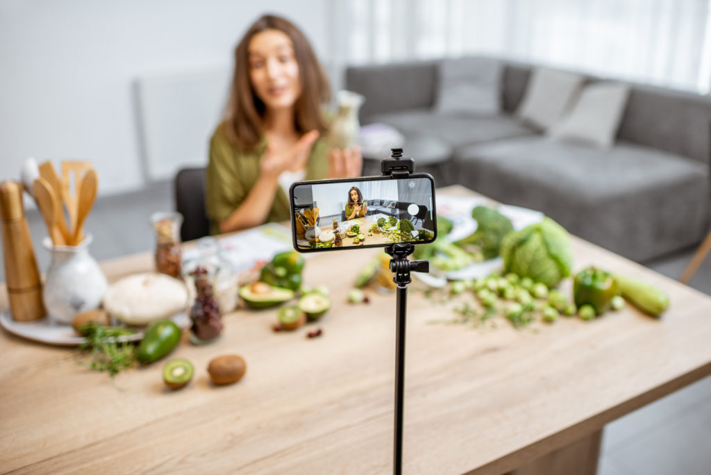 Young woman recording on a smart phone her vlog and sitting at the table with lots of green vegan food ingredients at home