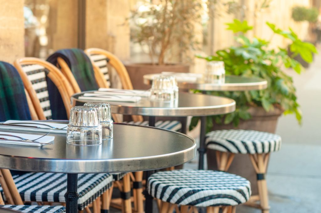 Charming outdoor sidewalk cafe in Paris, France with black and white chairs