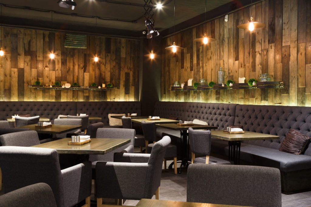 Cozy wooden interior of restaurant with gray chairs and sofas