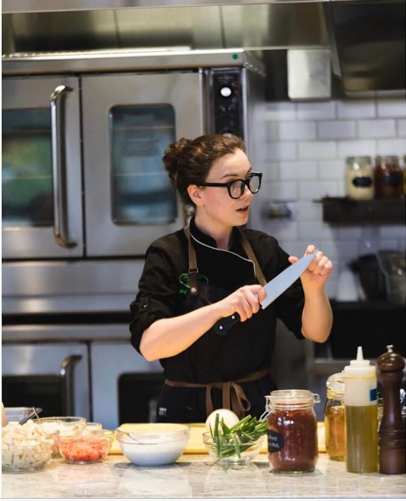 Escoffier Chef Instructor Stephanie Michalak White holding a knife while doing a cooking demo