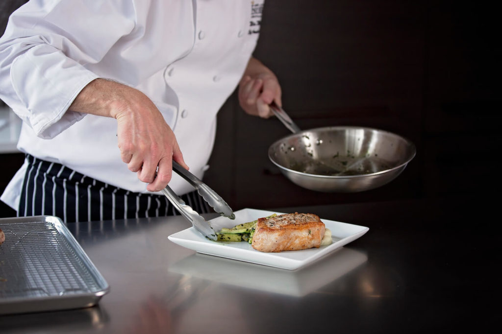 Chef using tongs to plate a meat and vegetable dish from metal pan