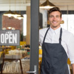Smiling man with apron standing next to door of restaurant with open sign