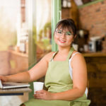 Smiling woman with glasses apron and laptop computer