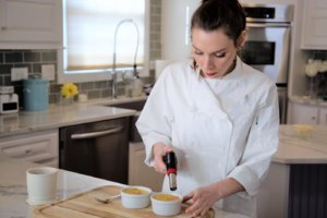 A woman uses a blowtorch on Creme Brule in the kitchen