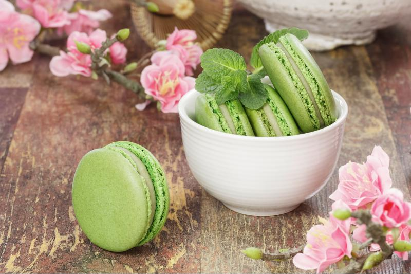A small bowl of matcha macarons sitting on a table.